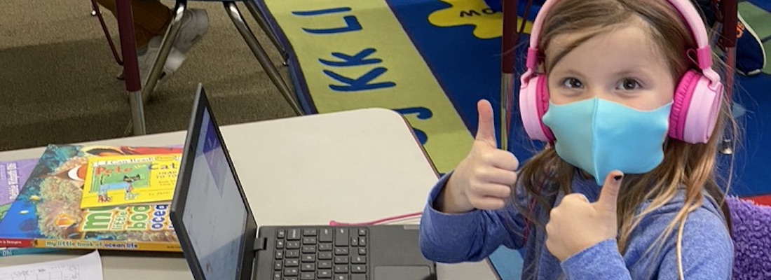 Student using laptop computer posing with 2 thumbs up